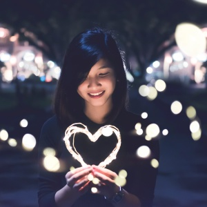 Woman holding heart-shape light