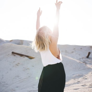 Woman walks in the sand and throws her hands up into the sun