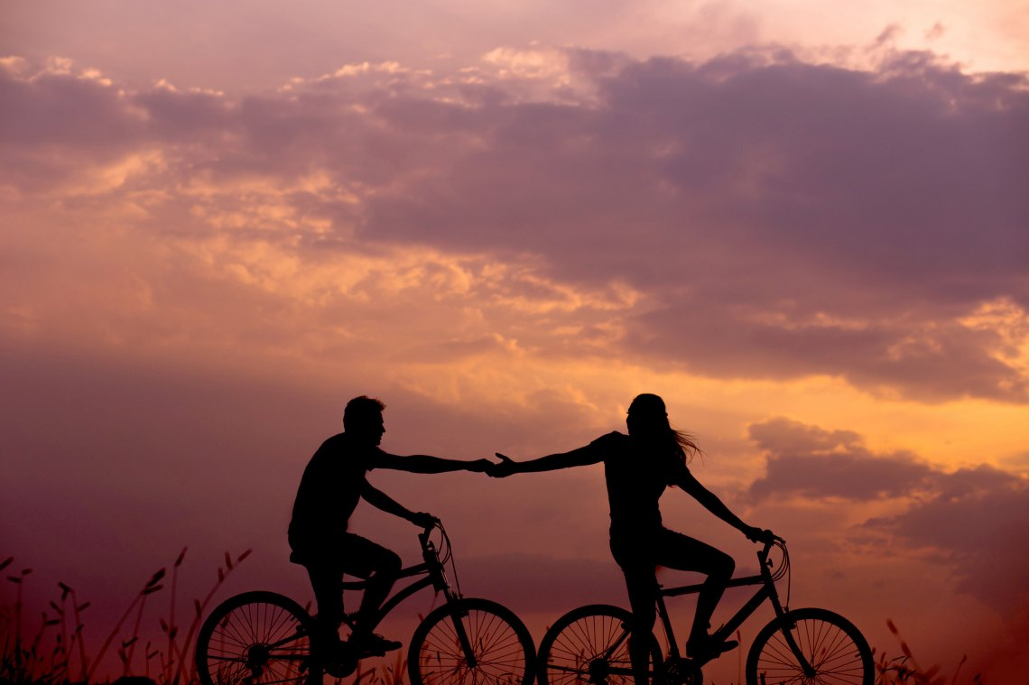 a woman and a man biking together while holding hands