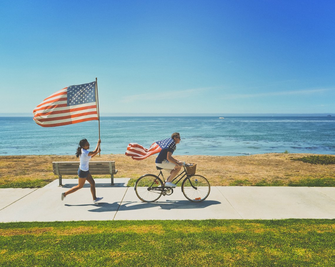 A man rides on a bike with an American flag draped over his shoulders while a woman runs after him holding an american flag