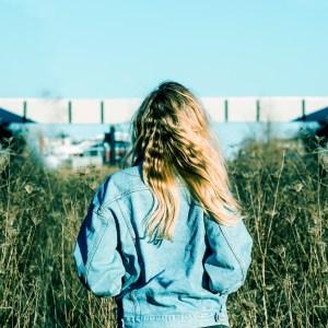 Woman wearing jean jacket in field