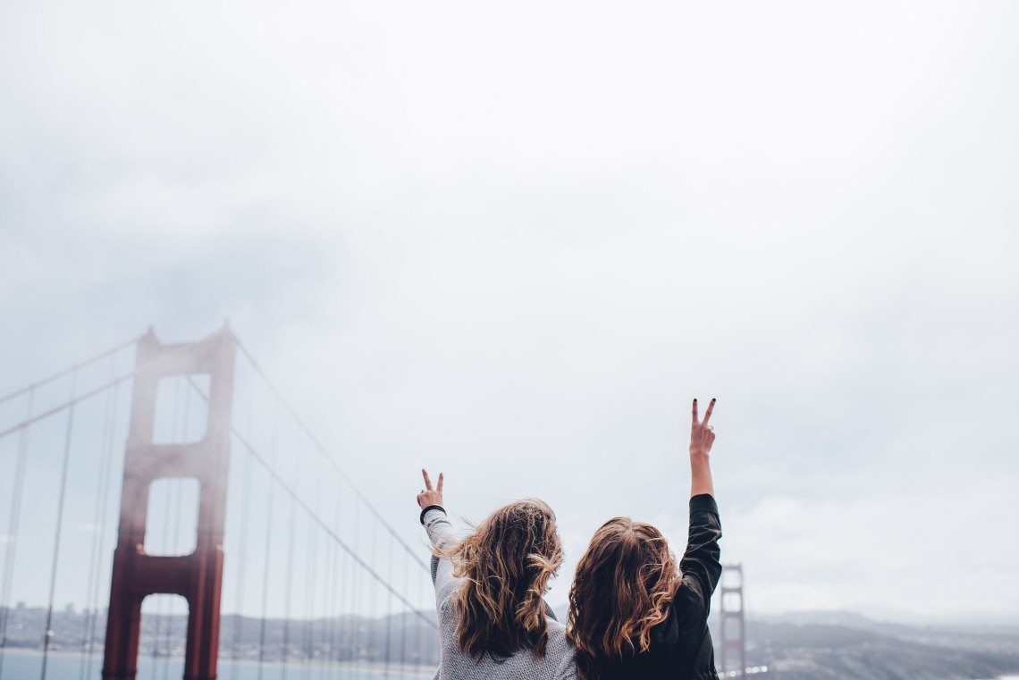 Two women stand in front of the San Francisco bridge, holding up peace signs