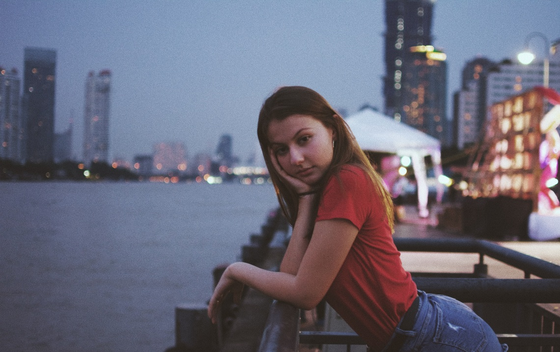 girl sitting by water and city, stop waiting, just go
