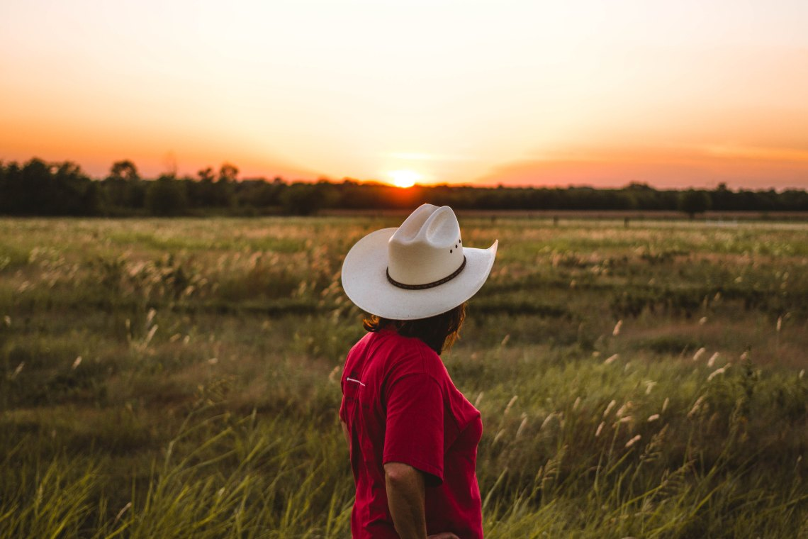 cowgirl in field, country artists you need to listen to