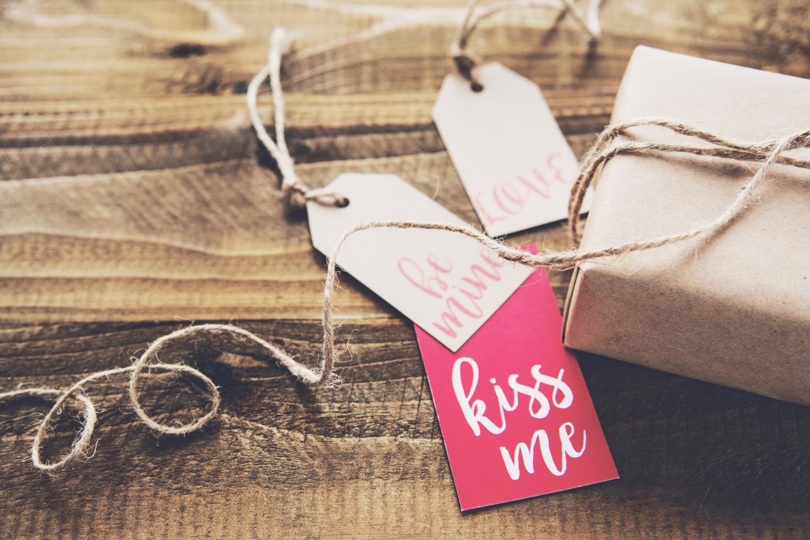 """A Christmas gift with tag that say """"Kiss Me"""", """"Be Mine"""" and """"Love"""""""