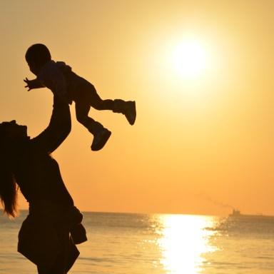 mom holding toddler sunset