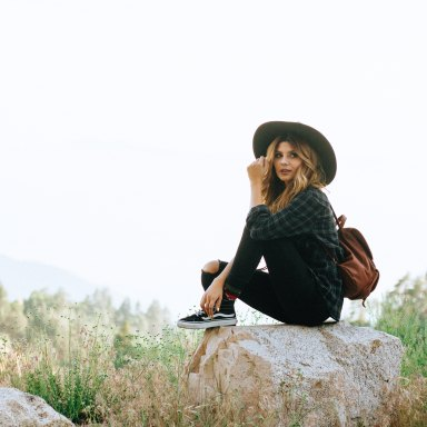 girl in hat sitting in nature