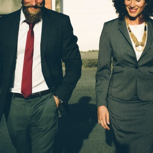 A man and woman in professional attire walk side-by-side