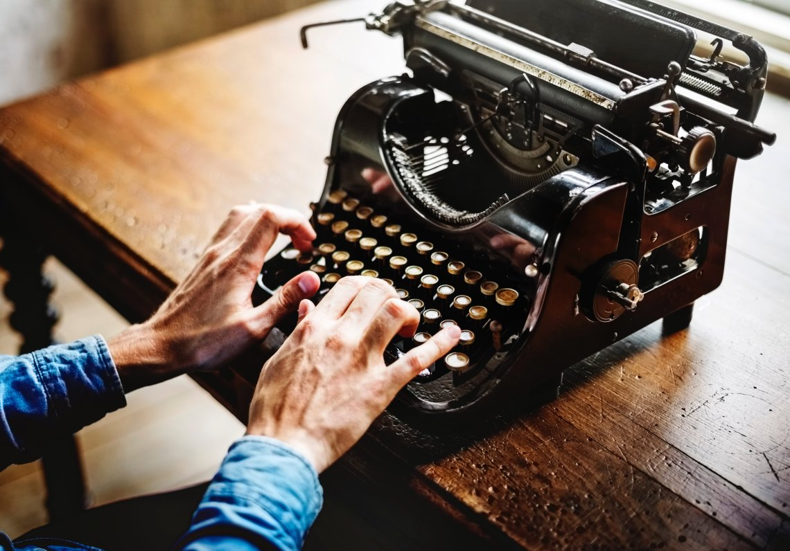 person types on a typewriter