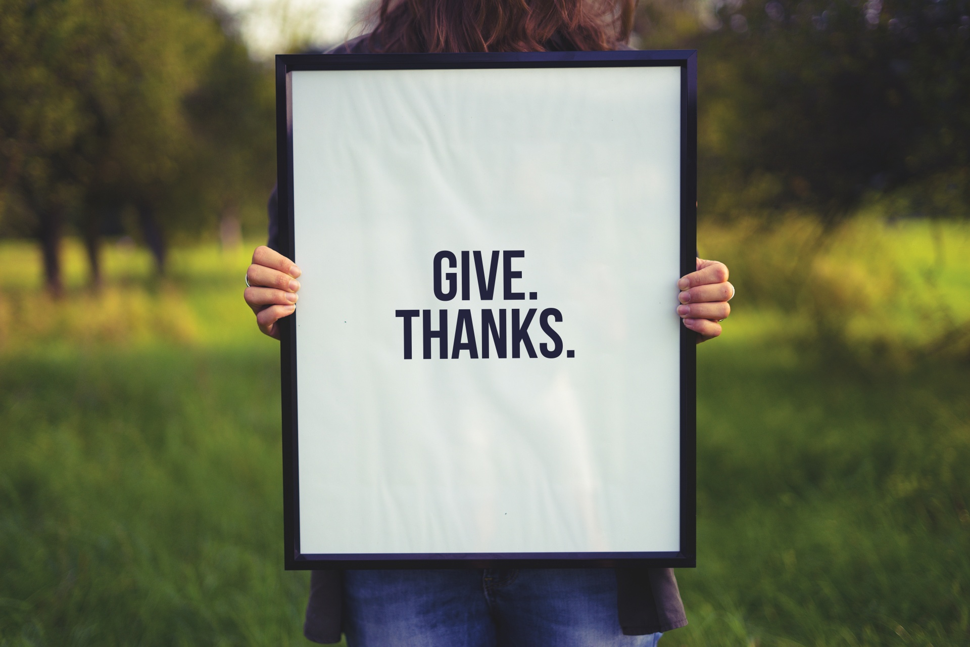 """A woman holds up a sign that says """"Give. Thanks."""""""
