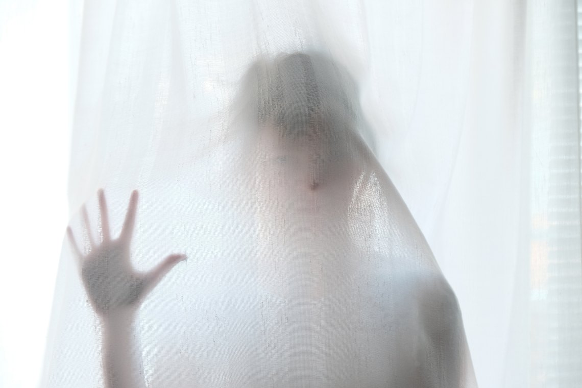 Woman stands behind a curtain, looking like a ghost