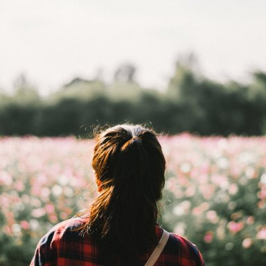girl in a field hair smiling