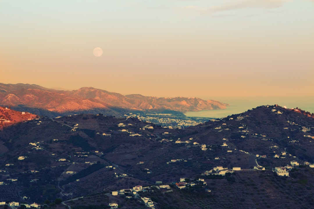 Full moon rises over a rural village overlooking the sea