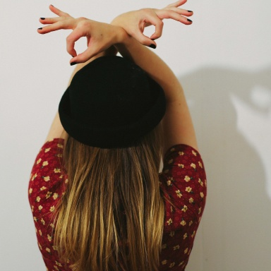 holding her hands about her head while wearing a hat