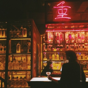 girl standing at a bar and neon signs alone