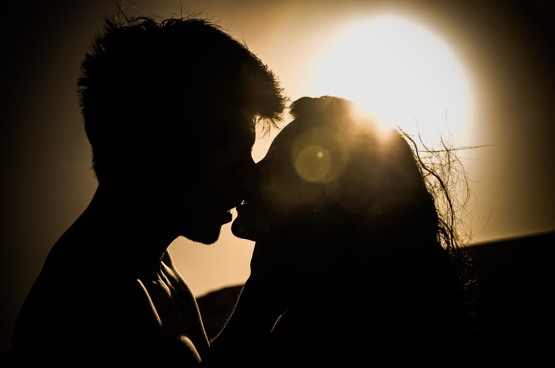 Classic sunset silhouette of couple kissing with sea wind frizzing their hair