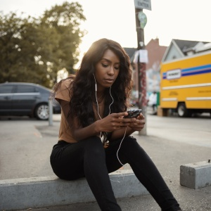 Occupied Young Woman Going Through Her Phone as She Listens to Music
