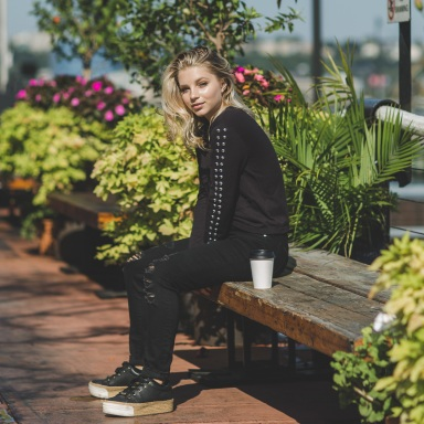 blond woman dressed sitting on a park bench with a paper cup beside her