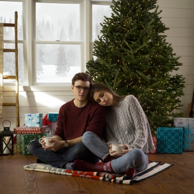 couple cuddling by tree with warm drinks