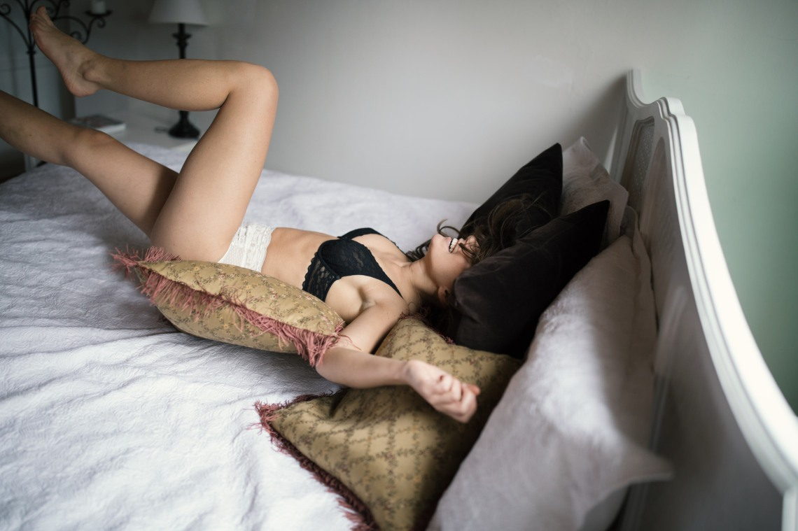 overjoyed girl jumping in bed in underwear