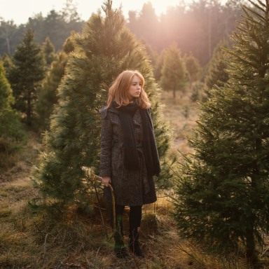 Lady Silently Stands among the Christmas Trees while Holding a Hand Saw