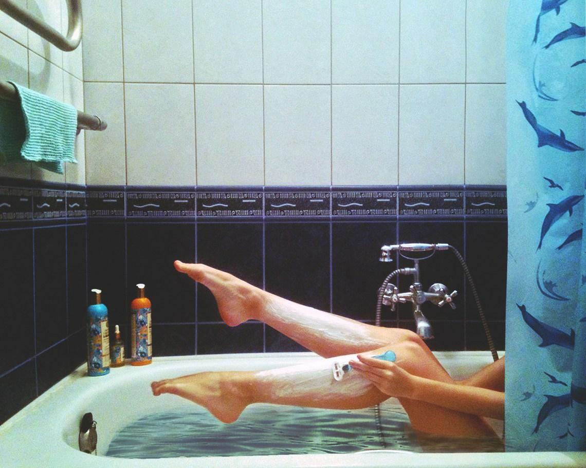 girl shaving her legs in bath tub