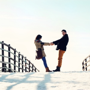 Man and woman hold hands on a snowy bridge