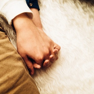 couple holding hands on white rug