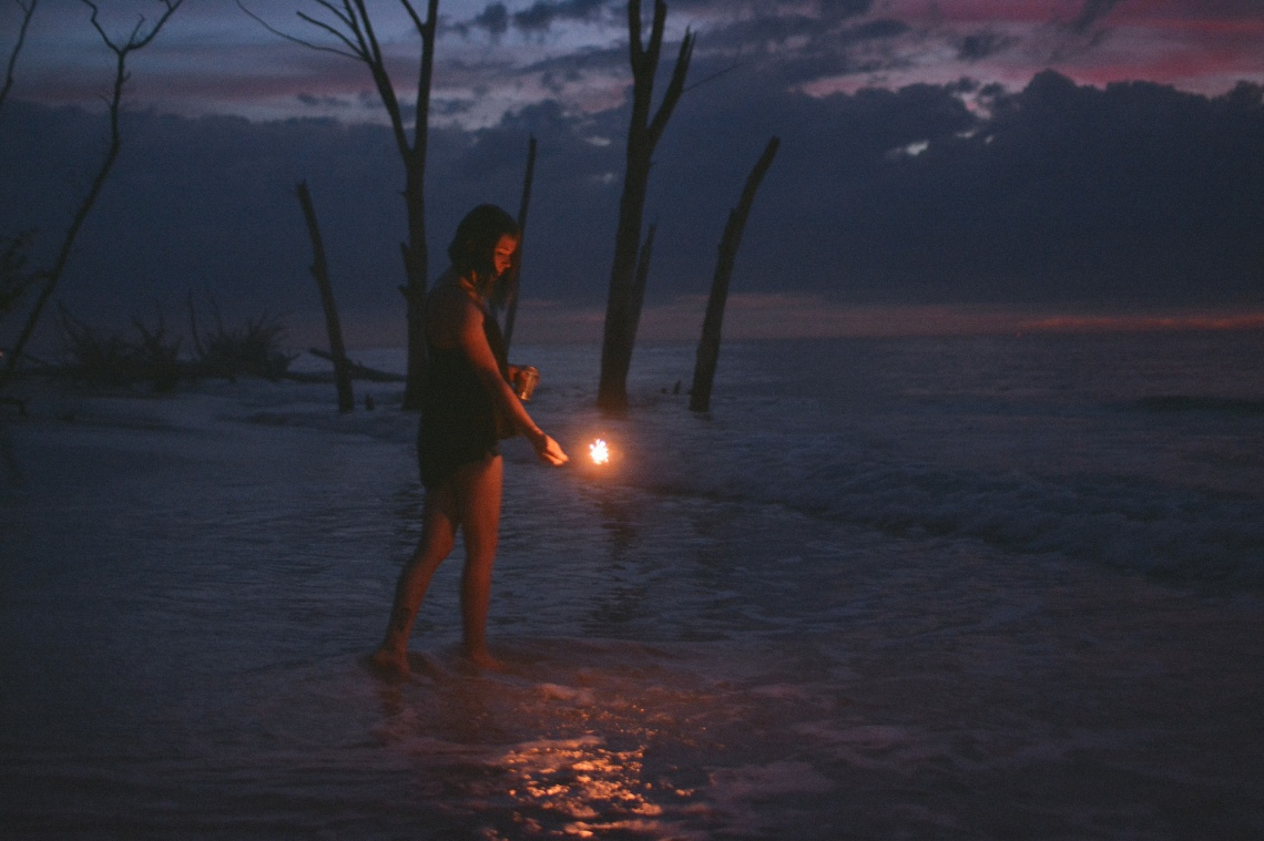 Girl playing with fire, sparkler standing in water with purples and blues of sunset reflecting, dead trees