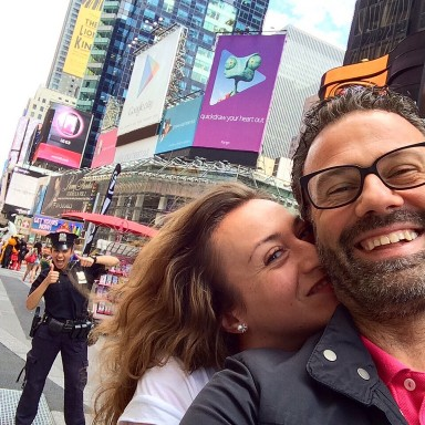 happy couple taking selfie in NYC with cop photobombing