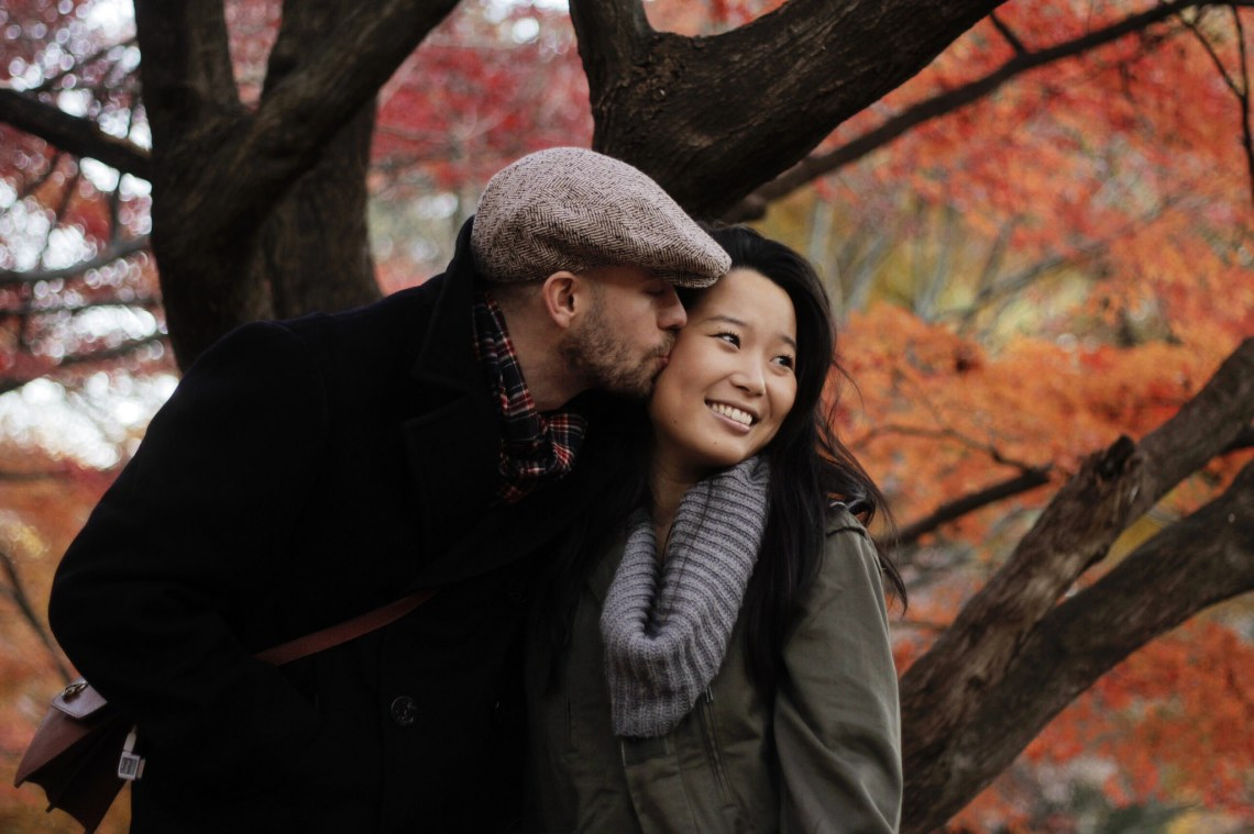autumn couple kissing on the cheek