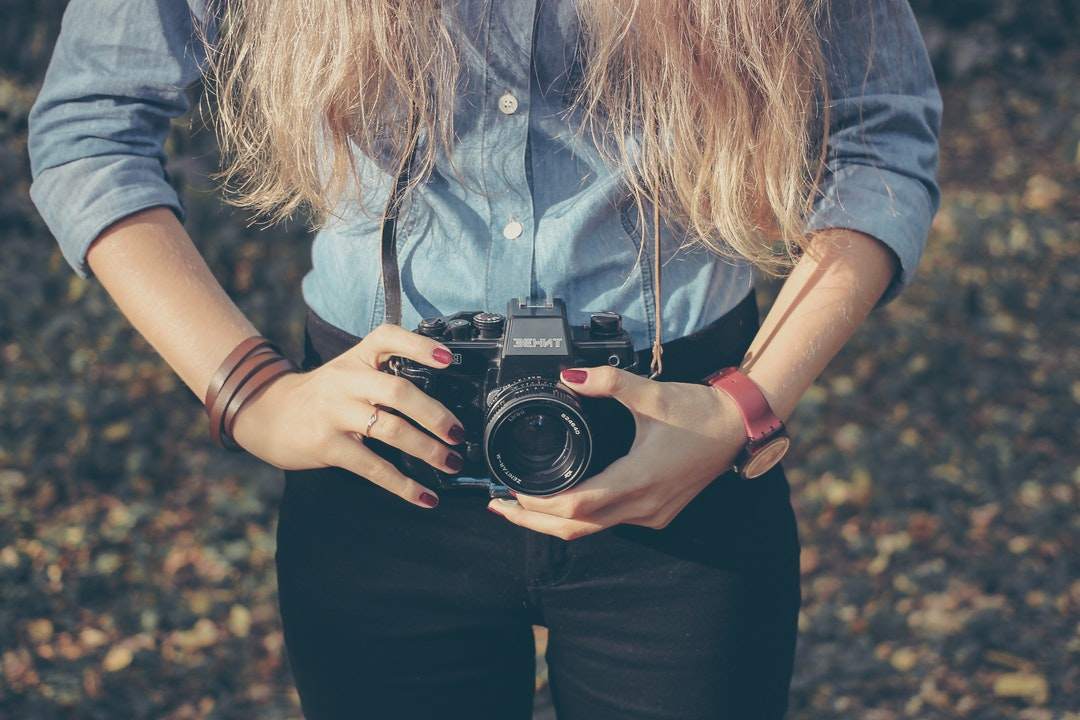 A close-up of a woman holding a Behnt Zenit camera.