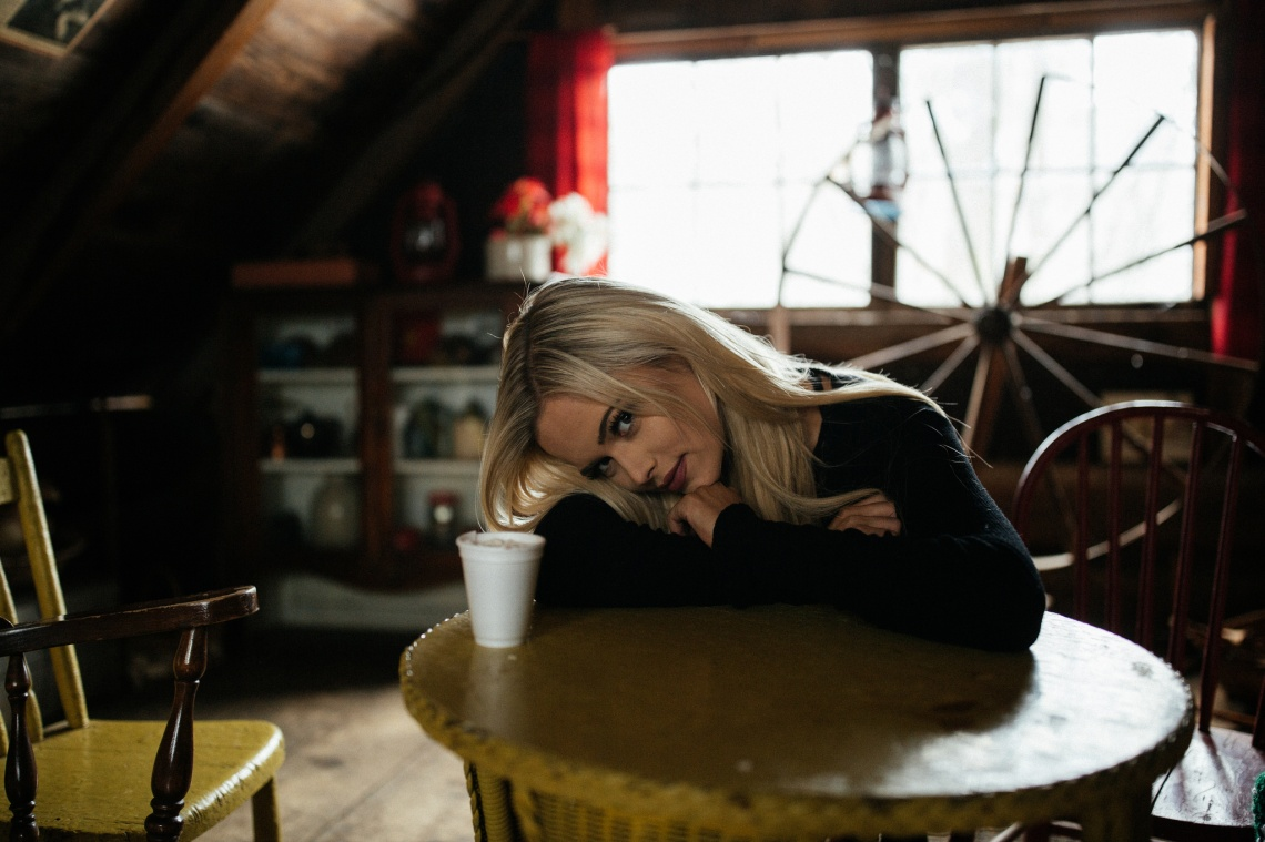 blonde girl in a cabin drinking coffee