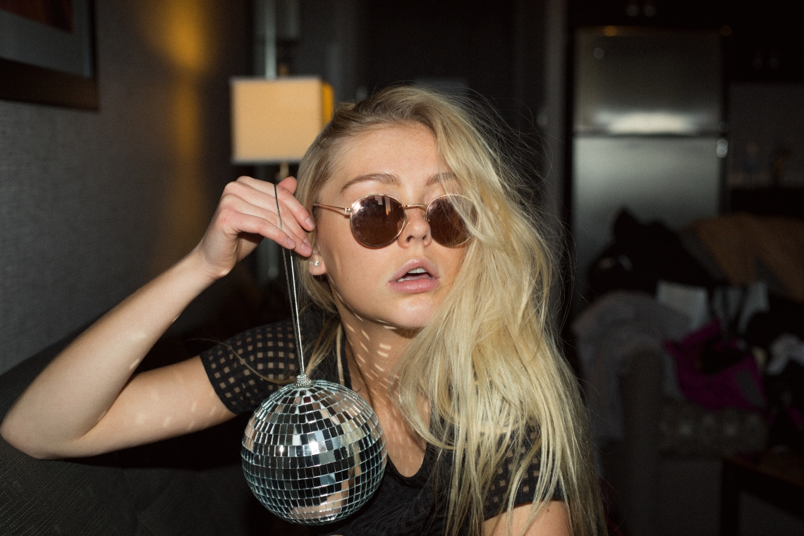woman in sunglasses holding disco ball