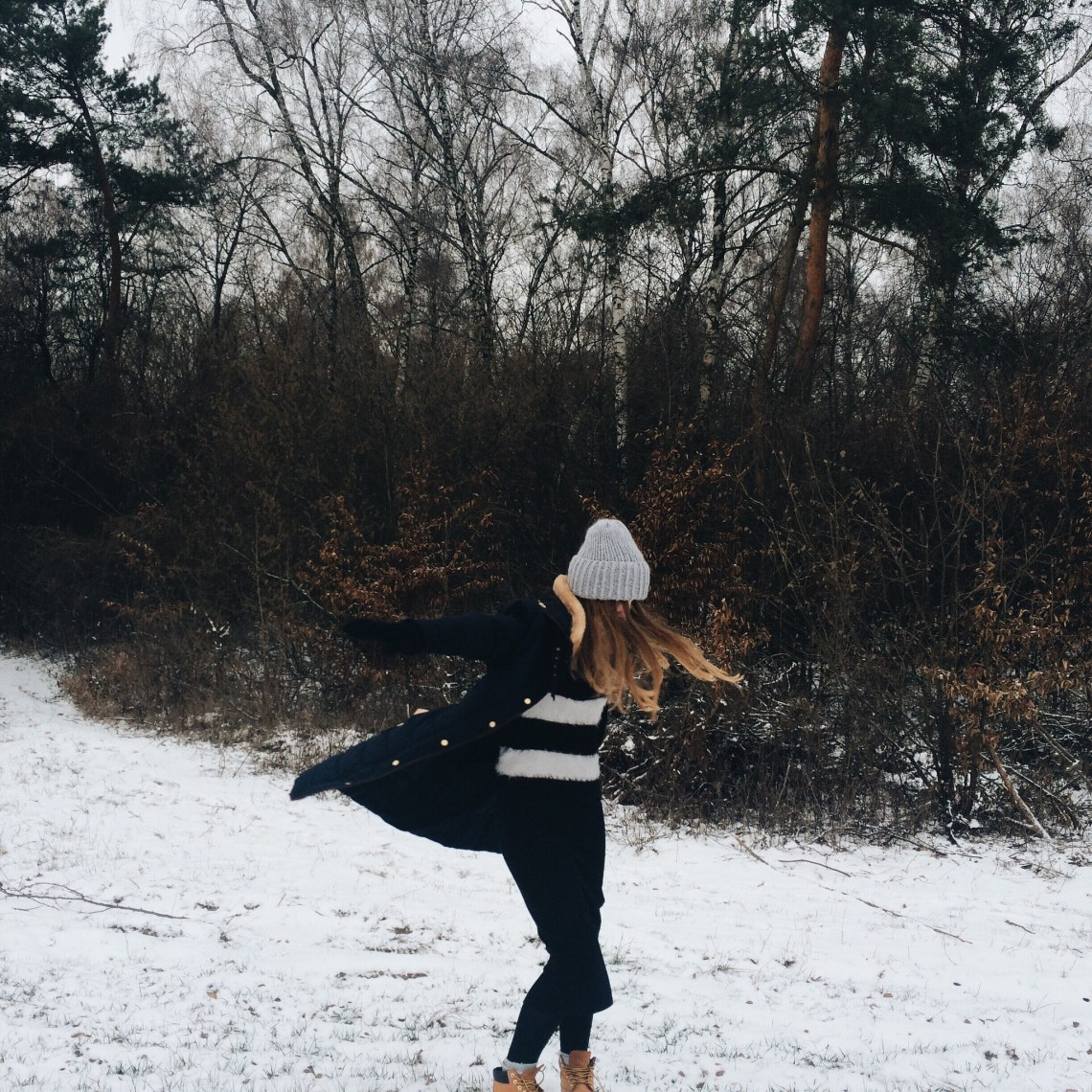 Frolicking in the snow, girl running down a snowy hill in winter