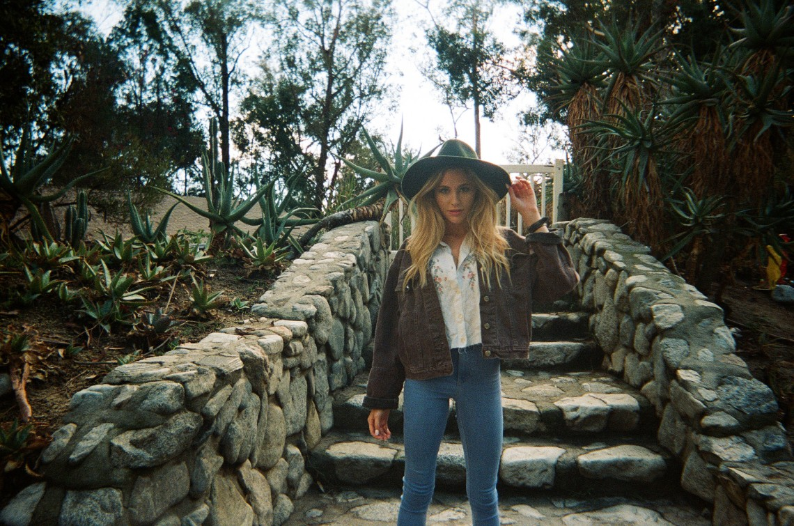Cool girl in a large hat standing on stone steps outdoors