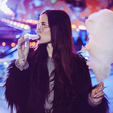 Goth girl eating fluffy pink cotton candy in her black furry jacket at an amusement park