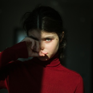 girl in a red turtleneck half lit