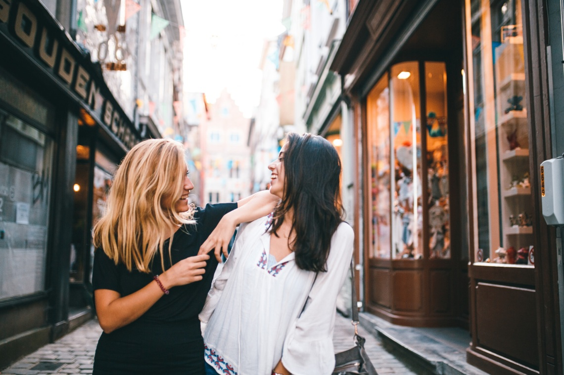 two friends laughing while walking down the street