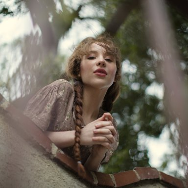 Lovely girl in braids looks down from the castle wall like Juliet Capulet