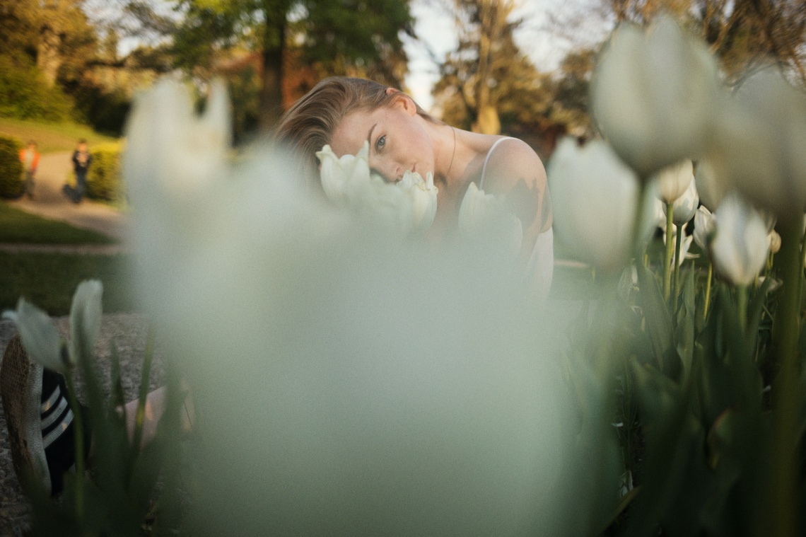 Beautiful young blonde gazing up seductively from behind white tulips