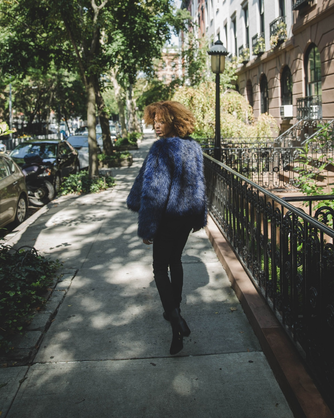 Woman with curly hair in a blue fur jacket looking back as she walks down the pavement