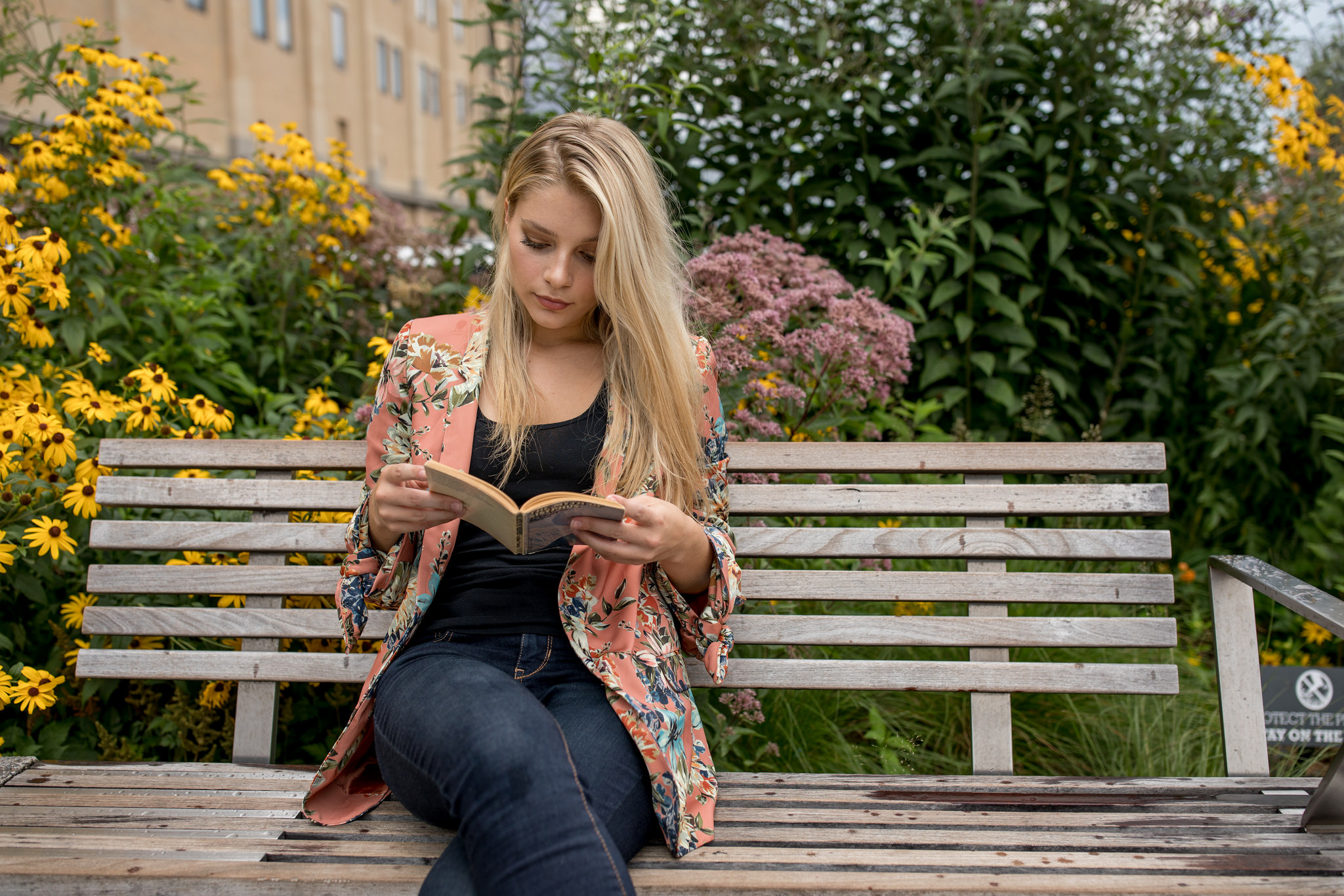 blonde young woman reading alone on bench