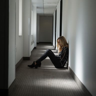 Young woman dressed in black sitting on the floor in a shadowy corridor