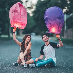couple sitting with lanterns in street