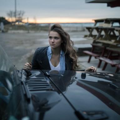 woman standing behind car