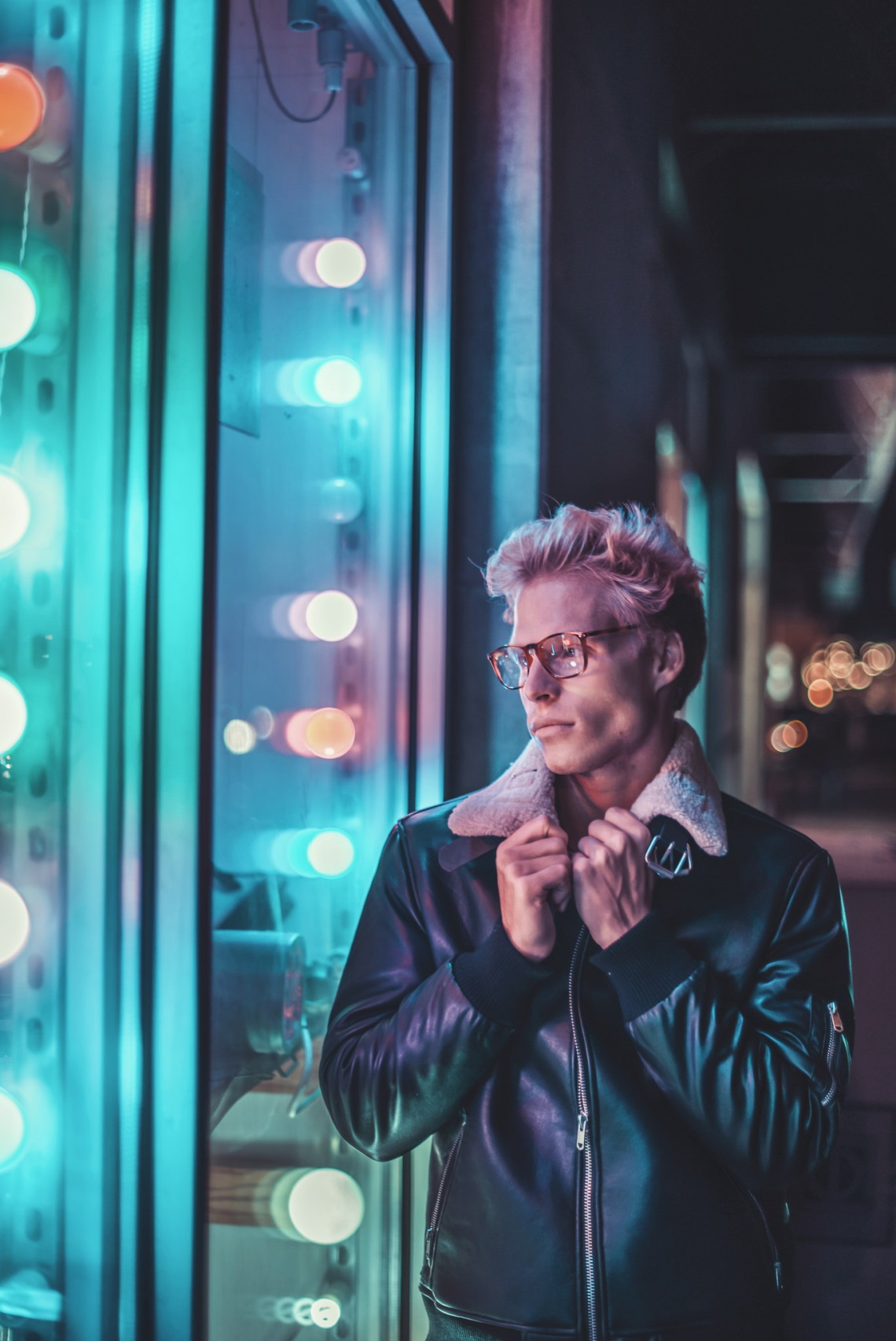 young man look into a window blue and pink lighting
