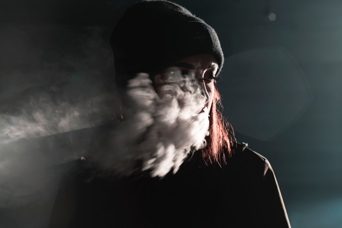 girl red hair smoke in her face