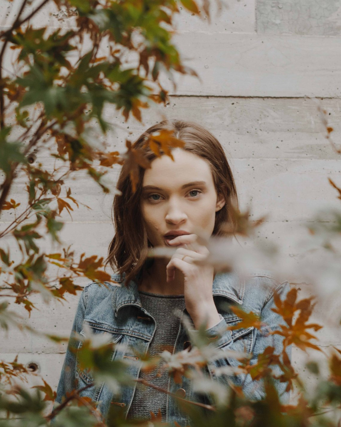 Woman peering from behind the leaves