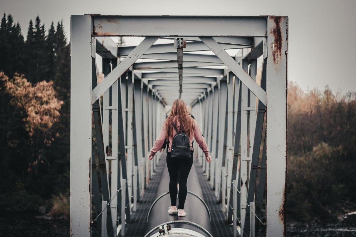 woman walking away on bridge